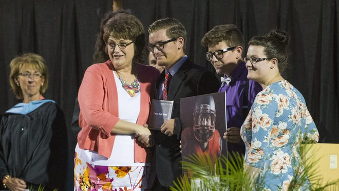Ben (left) and Whaelynn Flake (center) and Kaytlinn Hewitt, pose after receiving their brother Kyle Flake's diploma at Combs High in San Tan Valley, Ariz. May 23, 2017. Kyle died from injuries sustained in a car accident.