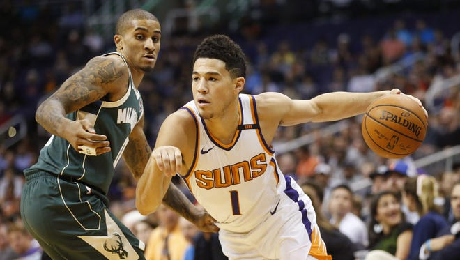 Phoenix Suns guard Devin Booker (1) drives around Milwaukee Bucks guard Gary Payton II (0) during the first quarter at Talking Stick Resort Arena in Phoenix, Ariz. November 22, 2017.