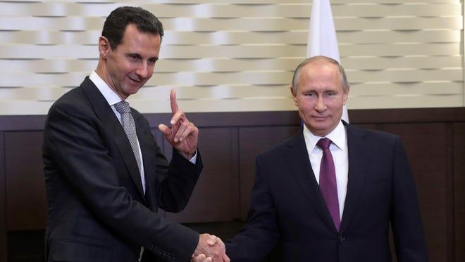 Russian President Vladimir Putin, right, shakes hands with Syrian President Bashar Assad in Sochi, Russia, on Nov. 20, 2017.