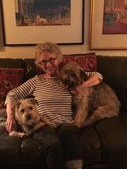 Tennessee artist Valerie Berlin snuggles with her two dogs, Woody (left) and Ella. The pups are mixed terriers and both are rescues.