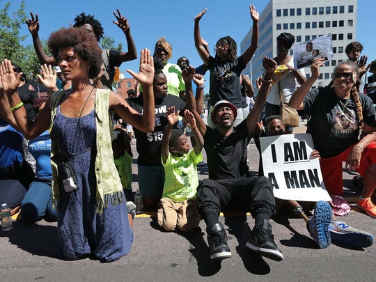 Protesters drop to their knees and put their arms in the air during a rally for Michael Brown Jr., who was shot and killed.