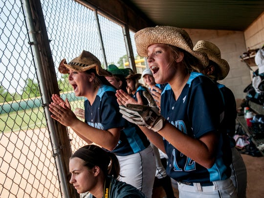 Richmond's Evelyn Swantek wears a cowboy hat and claps with her teammates in the dugout during a quarterfinal softball game Tuesday, June 13, 2017 at Novi High School.