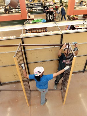 Ashon U. Ragan disassembles shelving with help from Angela Travis in the Miami Township Kroger store. The shelving is being removed to make way for cold beer coolers and a wine-tasting area.