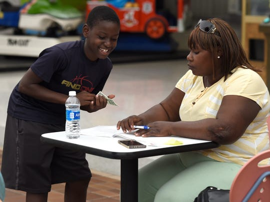 Angelo St. Louis, 11, shows his mother Marianie Sanon the dollar bill that he exchanged coins for as she fills out a job application at Washington Square Mall in Evansville recently.   Sanon was one of 21 Haitian passengers injured when the van they were being transported in wrecked on Interstate 69 while traveling to their worksite on Sept., 24, 2015. Two passengers died and several others, including Sanon, were severely injured.