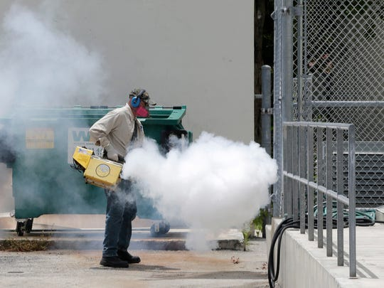 A Miami-Dade County mosquito control worker sprays