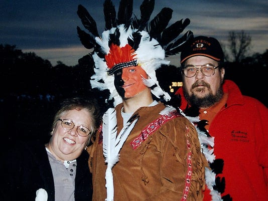 2003.8.15.12 MASCOT METRO: HANDOUT PHOTO: Anthony Wurster 19, former Anderson Redskin mascot, poses with his parents Sylvia and Edward Wurster, on senior night at an Anderson High School football game. Wurster was the school's mascot, a Redskin, for five years before graduating this year. The school is eliminating the mascot, but a Native American student is challenging the decision. Friday August 15, 2003. COPY PHOTO The Cincinnati Enquirer / COPIED BY Brandi Stafford .b.s