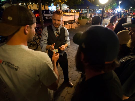 Social underground cocktail bar doorman Mitchell Armstrong checks patron's IDs on Friday, June 15, 2018, in Old Town Fort Collins, Colo.