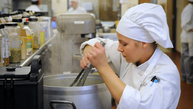 Culinary arts student Ashley Harden stirs soup May 7 for lunch service at the St. Cloud Technical & Community College.