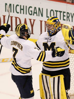 Michigan goalie Steve Racine, right, celebrates with JT Compher (7) after a 3-2 win over Northern Michigan at the Great Lakes Invitational college hockey game Tuesday.