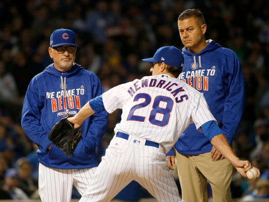 Chicago Cubs manager Joe Maddon, left, checks on starting pitcher Kyle Hendricks (28) after Hendricks was hit by a ball on his arm in the fourth inning of Game 2 of baseball's National League Division Series, Saturday, Oct. 8, 2016, in Chicago. (AP Photo/Nam Y. Huh)