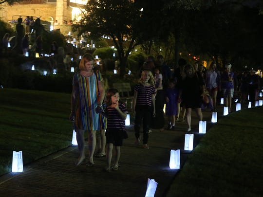 Attendees walk among luminary bags placed around the