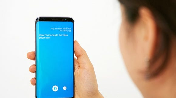 A woman holding the Galaxy S8 using Bixby.