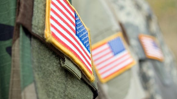 Shoulders of camo uniforms with U.S. flags on them.