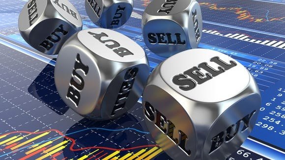 Dice labeled BUY and SELL on top of an LCD screen showing stock charts and data
