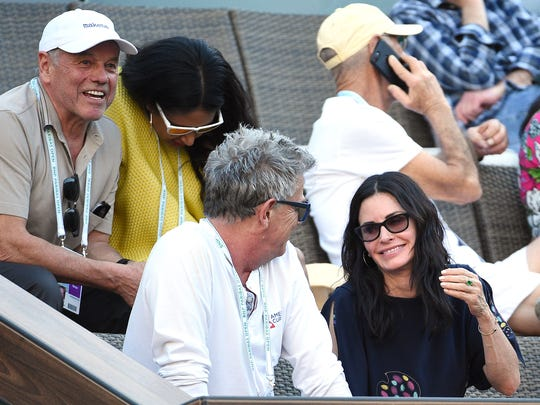 Celebrity chef Wolfgang Puck (L) wife, designer Gelila Assefa, actress Courtney Cox (R) and musician/record producer David Foster attend the Venus Williams and Jelena Jankovic tennis match on Center Court at Indian Wells Tennis Garden on March 11, 2017 in Indian Wells, California.