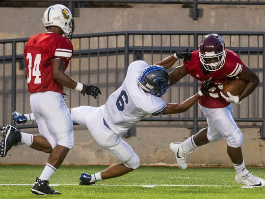 North defender Kevin Shaw, of Colbert Heights, tackles South running back Davede Herron, of Benjamin Russell, during the AHSAA All Star Sports Week Football Game at Cramton Bowl in Montgomery, Ala. on Thursday July 19, 2018.