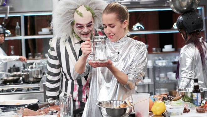 Host Alton Brown watches Chef Natalie Beck (Locketz) prepare her Round 1 dish, Bloody Mary with Slider and a Bacon Wrapped Date with Olive Accouterments, in the sabotage element of 'Culinary Costumes' on the Food Network's 'Cutthroat Kitchen.'