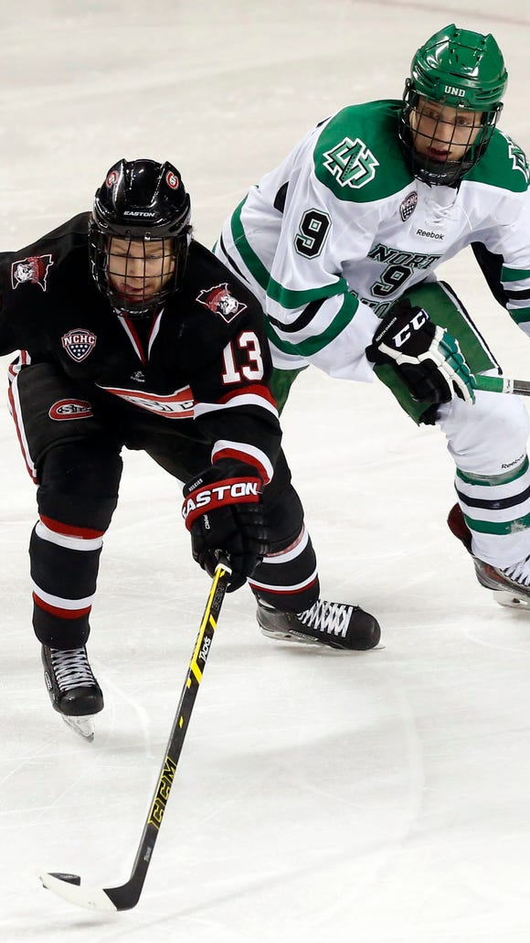 St. Cloud State's David Morley is chased by North Dakota's Drake Caggiula on Friday at Ralph Engelstad Arena in Grand Forks, N.D.