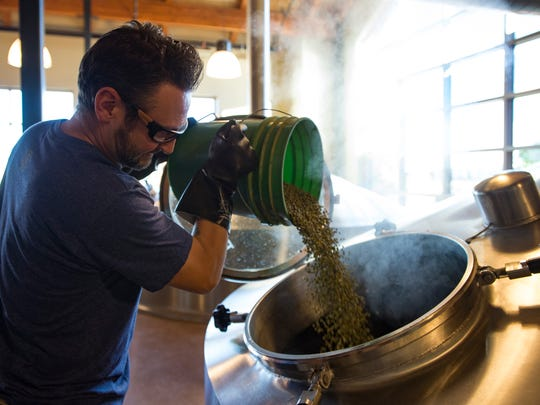 Johnny Benson adds hops to a brewing kettle at Odell Brewing Co. in Fort Collins.