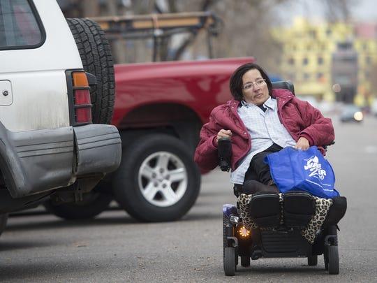 Vivian Armendarez steers her electric wheelchair around vehicles parked on Matthews Street as she runs errands in Old Town on Tuesday, March 21, 2017. Armendarez said she sometimes feels safer traveling in the street instead of uneven sidewalks.