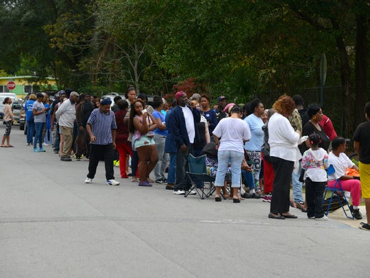 Folks stand in line Saturday during the Reggie Evans Foundation annual Turkey Giveaway at Woodland Heights Community Resource Center. 400 bundles with a turkey, stuffing and greanbeans were given away along with 400 more bundles at the Fricker Center.
