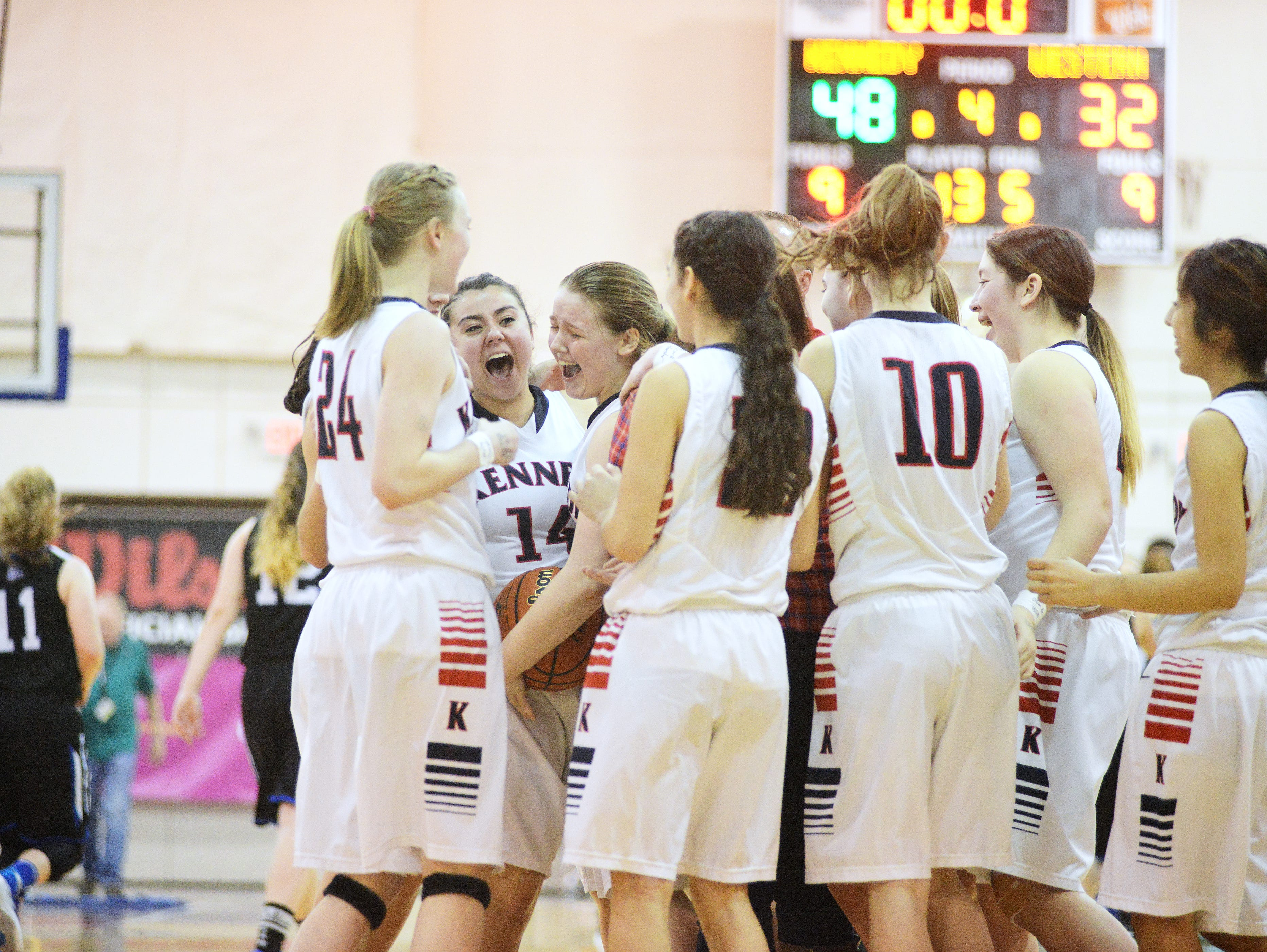 The Kennedy Trojans celebrate their 48-32 win against Western Mennonite on Friday in the state 2A basketball tournament in Pendleton.