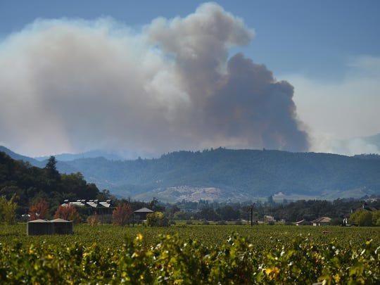 A wildfire burns in the mountains to the west of the