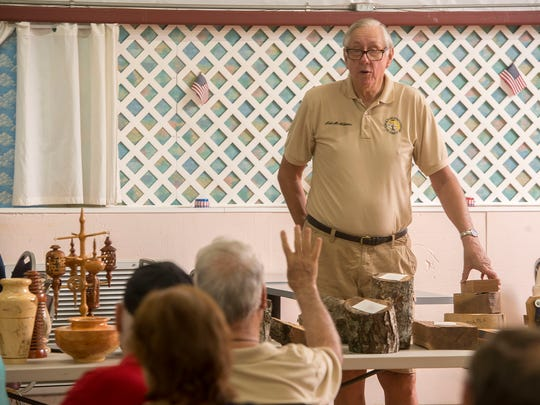 Woodturner Neil McWilliams conducts an auction July 21 during the Artistic Woodturners of Northwest Florida's meeting at Ragon Hall.