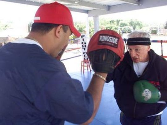 Dr. Stephen Schuster, right, hits the mitts with El Paso Fight Club trainer and former professional fighter Herman Delgado Saturday morning at  Schuster's personal home ring. The El Paso Fight Club caters to white collar clientele who want to achieve a dynamic, more athletic physique.