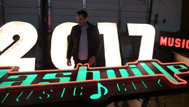 Jonathan Hammel, owner of MadeFirst, walks by the Nashville'd New Year's Eve new 2017 sign at the company's warehouse in Nashville on Dec., 14, 2016.