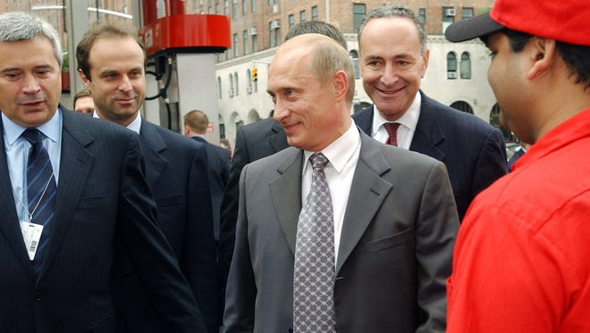 "In this Sept. 26, 2003, file photo, Russian President Vladimir Putin, center, and Sen. Charles Schumer D-N.Y., second from right, are escorted through New York's first Lukoil gas station by Lukoil President Vagit Alekperov, left, in New York City. Lukoil is the giant Russian oil company. Putin later traveled to meet with President George W. Bush at the Camp David presidential retreat. President Donald Trump, his administration under siege for contacts with Russian officials, is calling for ""an immediate investigation"" into Schumer tie's to Russian Putin. Trump's evidence? A 14-year-old photo of Schumer and Putin holding coffee and doughnuts in a New York City gas station."