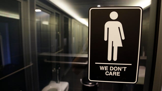 In this photo taken Thursday, a sign is seen outside a restroom at 21c Museum Hotel in Durham, N.C. The Obama administration Friday ordered school districts across the nation to let transgender students use the bathroom of their choice.
