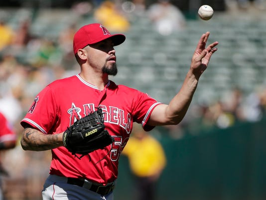 Los Angeles Angels starting pitcher Hector Santiago throws to first base to put out Oakland Athletics Sam Fuld on a ground ball during the first inning of a baseball game on Wednesday, Sept. 24, 2014, in Oakland, Calif. (AP Photo/Marcio Jose Sanchez)