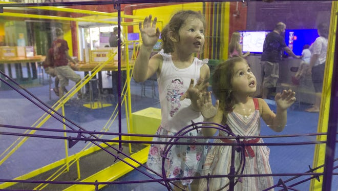 Ava Lin, 4, left, and sister Reese, 2, explore the Imaginarium, one of the city-run facilities considered for private management.