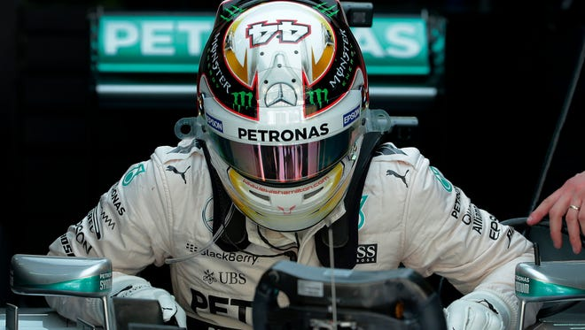 Mercedes driver Lewis Hamilton of Britain gets up from his car after after the second practice session for the Malaysian Formula One Grand Prix.