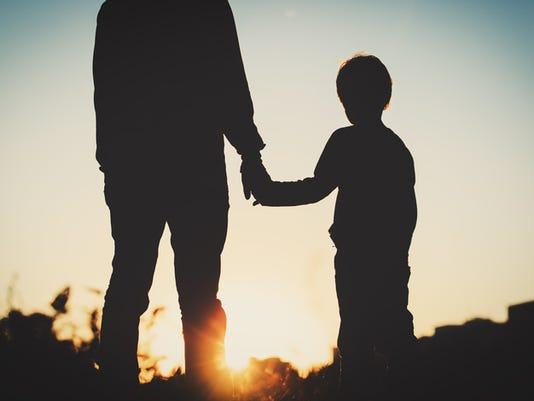 silhouette of father and son holding hands at sunset