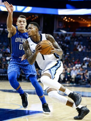 Memphis Grizzlies' Jarell Martin (right) drives the lane against the Orlando Magic defender Aaron Gordon (left) during first quarter action at the FedExForum in Memphis, Tenn., Monday, October 2, 2017.