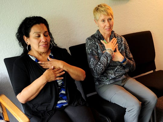 Beatrice Rodriguez (left) and Ronda Wilson perform self reiki on the heart at Shiatsu Wellness Center in Salem.