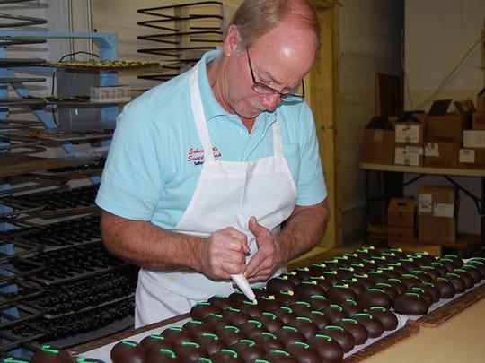 Schneider's Sweet Shop owner Jack Schneider, decorates