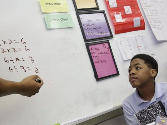 A fifth-grade teacher explains a math problem to Anthony Lewis at Detroit Merit Charter Academy in Detroit last year.