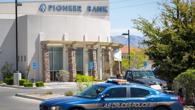 A police car cordons off the parking lot of Pioneer Bank on University Avenue on March 26, 2016. Las Cruces police are investigating a robbery that occurred that morning at the bank.