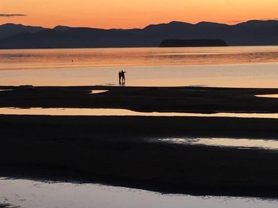 A couple wades into a sandy stretch of Burlington Bay