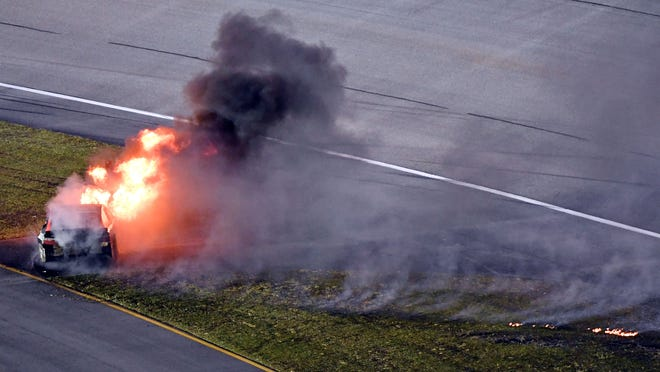 The car of NASCAR Sprint Cup Series driver Martin Truex Jr. (78) catches fire after a wreck during the Ford Ecoboost 400 at Homestead-Miami Speedway.