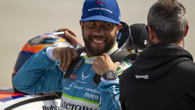 Bubba Wallace gets ready to enter his car for qualifying rounds before a 2019 NASCAR Xfinity Series auto race in Dover, Del. Denny Hamlin is starting his own race car team in partnership with Charlotte Hornets owner Michael Jordan and Wallace as the driver.