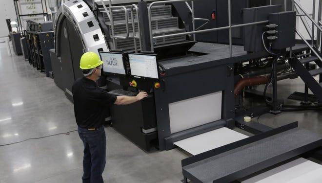 Jason Frohn, lead digital operator at Great Northern StrataGraph in Oshkosh, does a test run on a new HP digital press. Joe Sienkiewicz / USA TODAY NETWORK-Wisconsin