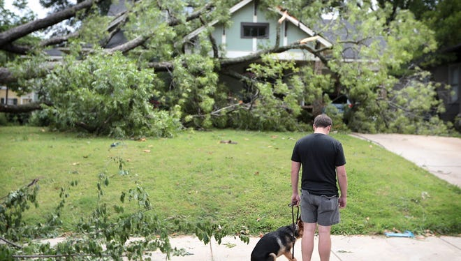 A Resident of McLean Ave. walks by a neighbors home buried under a downed tree Sunday morning after a severe thunderstorm knocked out power to most of Memphis Saturday night