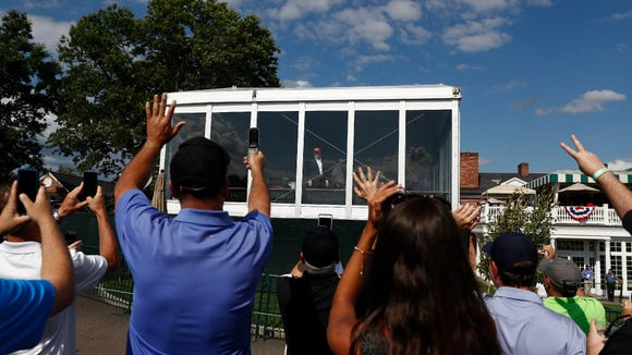 Spectators wave to President Trump - who waved back - during Saturday's third round of the U.S. Women's Open at Trump National Golf Club in Bedminster, N.J/