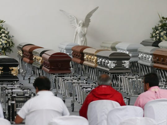 Journalists sit before coffins containing the remains of Chapecoense soccer team members who died in an airplane crash, in Medellin, Colombia, Thursday, Dec. 1, 2016. Forensic authorities say they have managed to identify a majority of the victims of Monday's crash and hope to finish their work on Thursday. (AP Photo/Fernando Vergara)