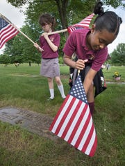 Kimora Friend places a flag on a veteran's grave at Holy Savior Cemetery in advance of Memorial Day.