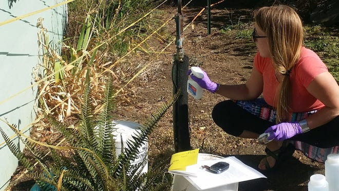 Paige Evans, with the Oregon Department of Environmental Quality, samples a well on the north coast.